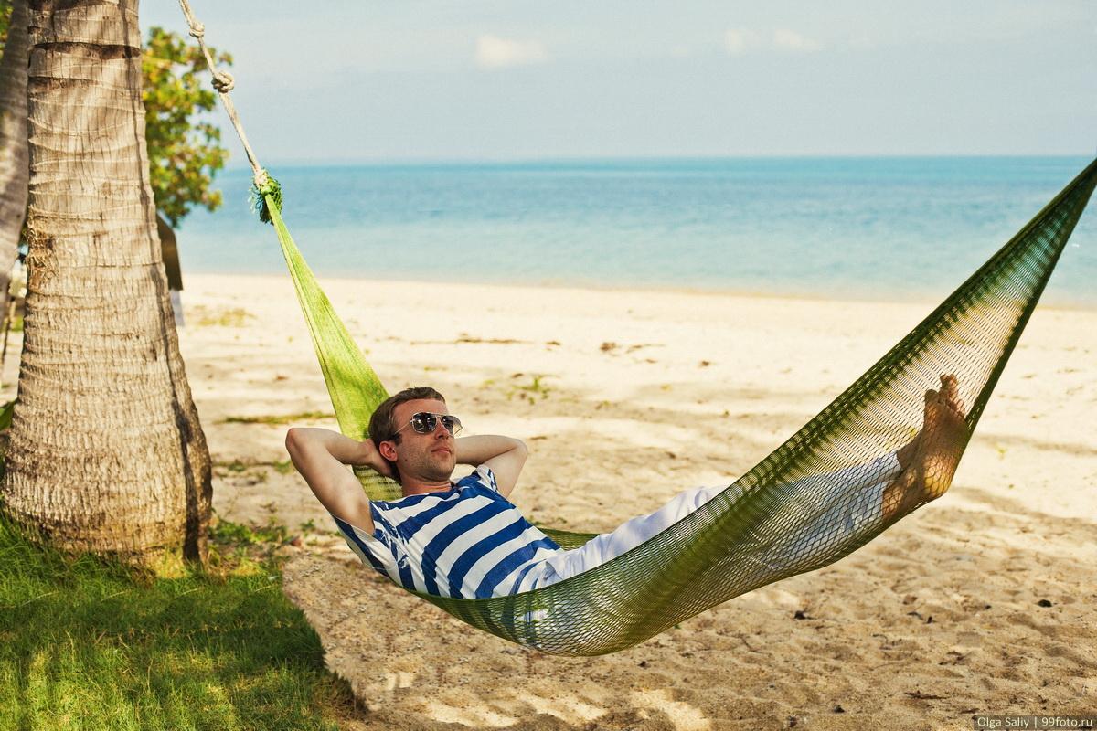 A man in a hammock under a palm tree