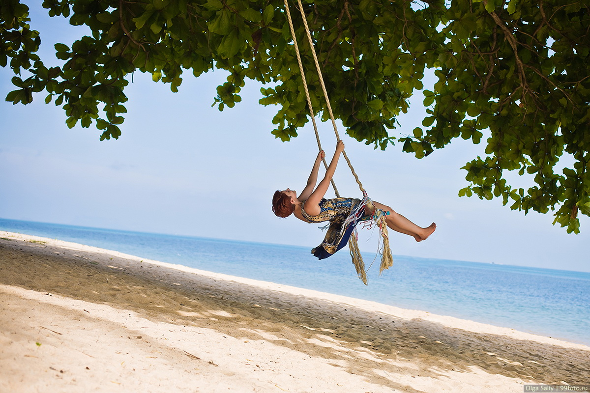 The girl on a swing on the beach