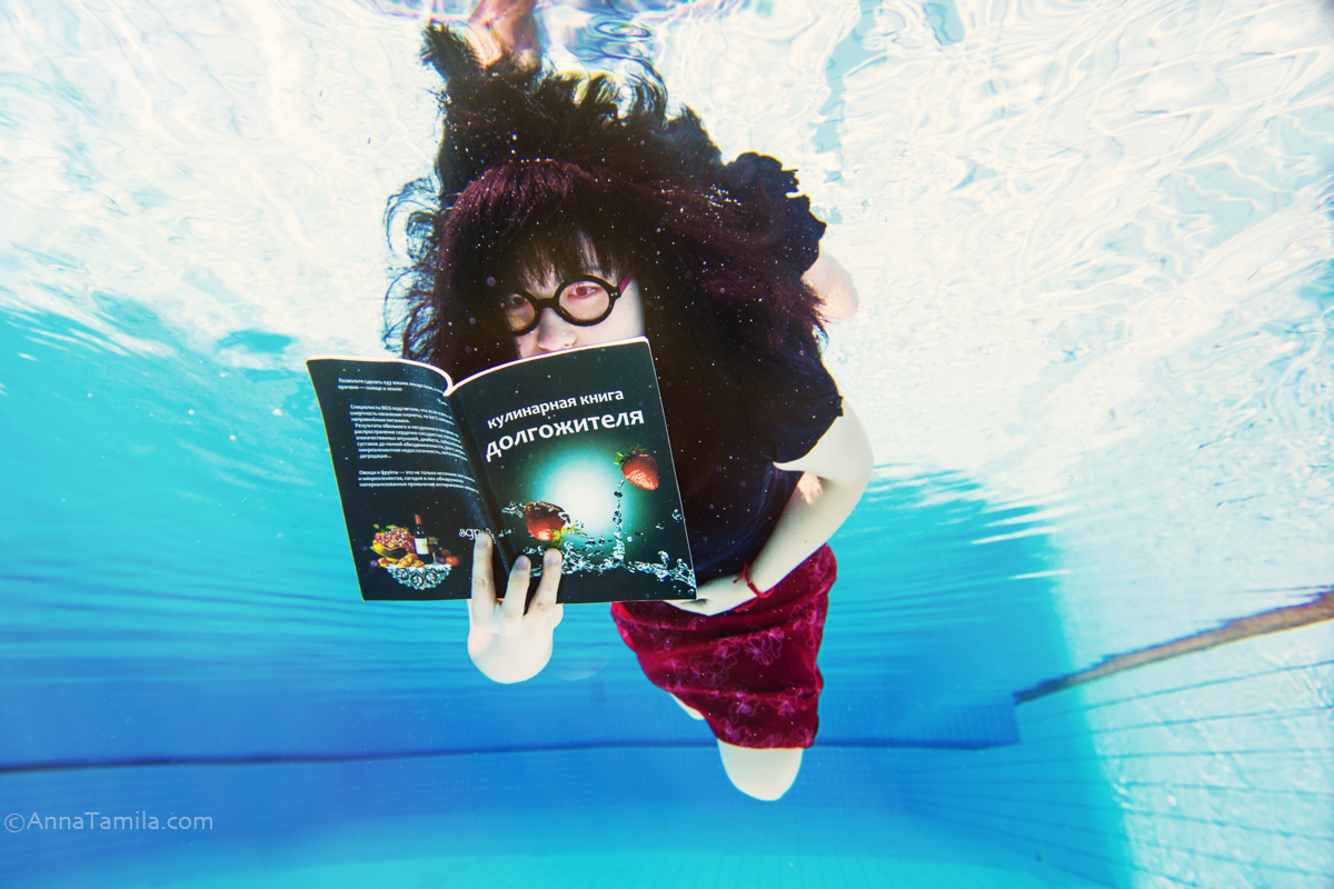 Asian young woman in business clothes and glasses with book under water