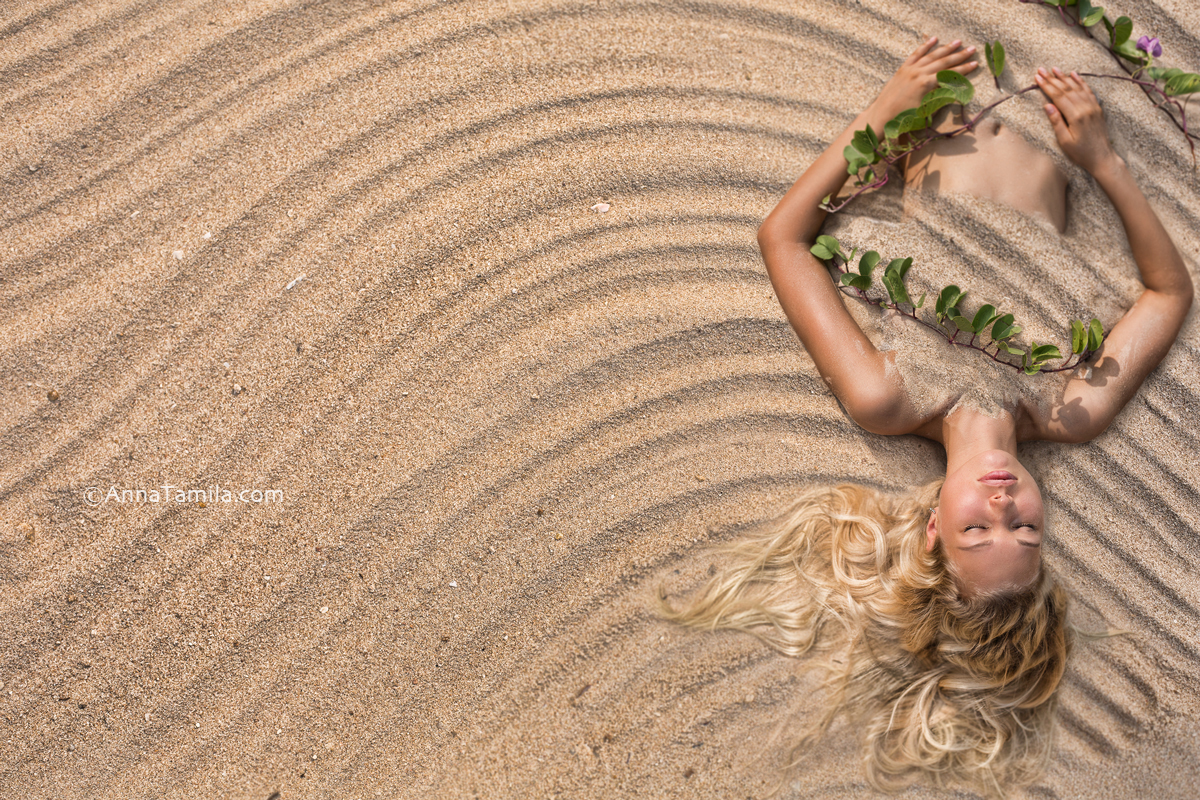 Fashion portrait of beautiful woman lying at the beach