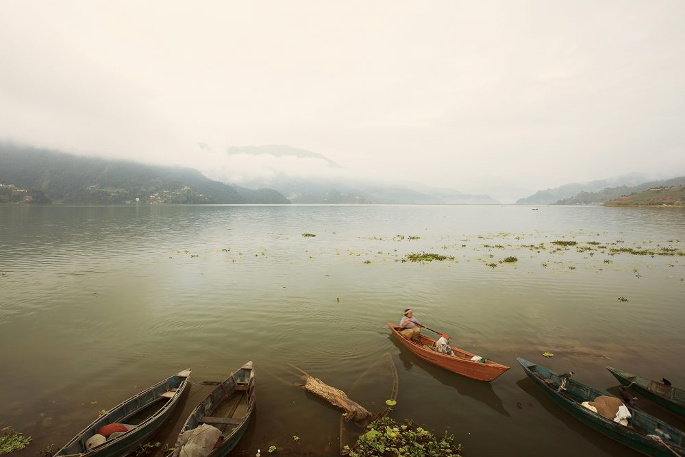 Boats on mountain lake in clouds, smoke and fog. Calm landscape