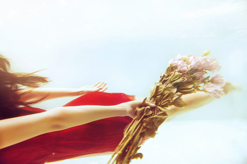 Woman in red dress swimming underwater with roses flowers
