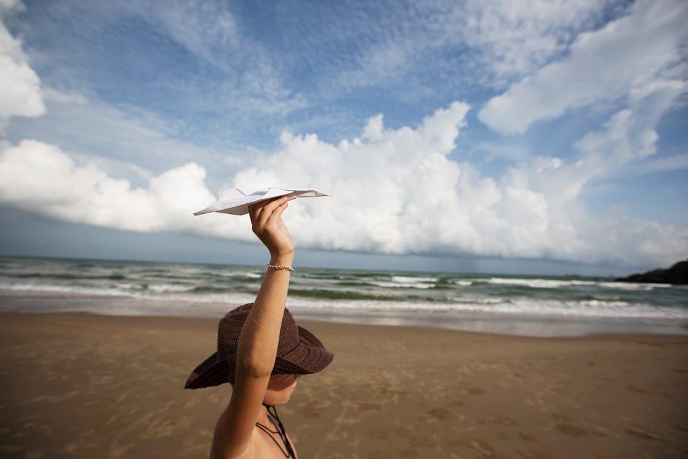 Little boy on ocean beach with paper plane