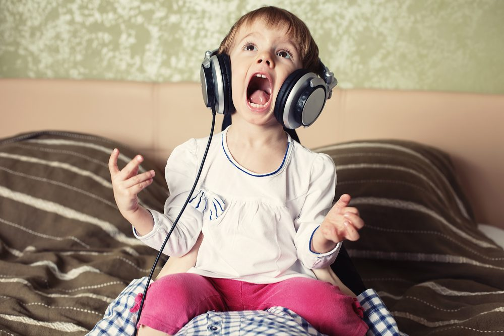 Happy little girl kid with headphone listen to music and sing song