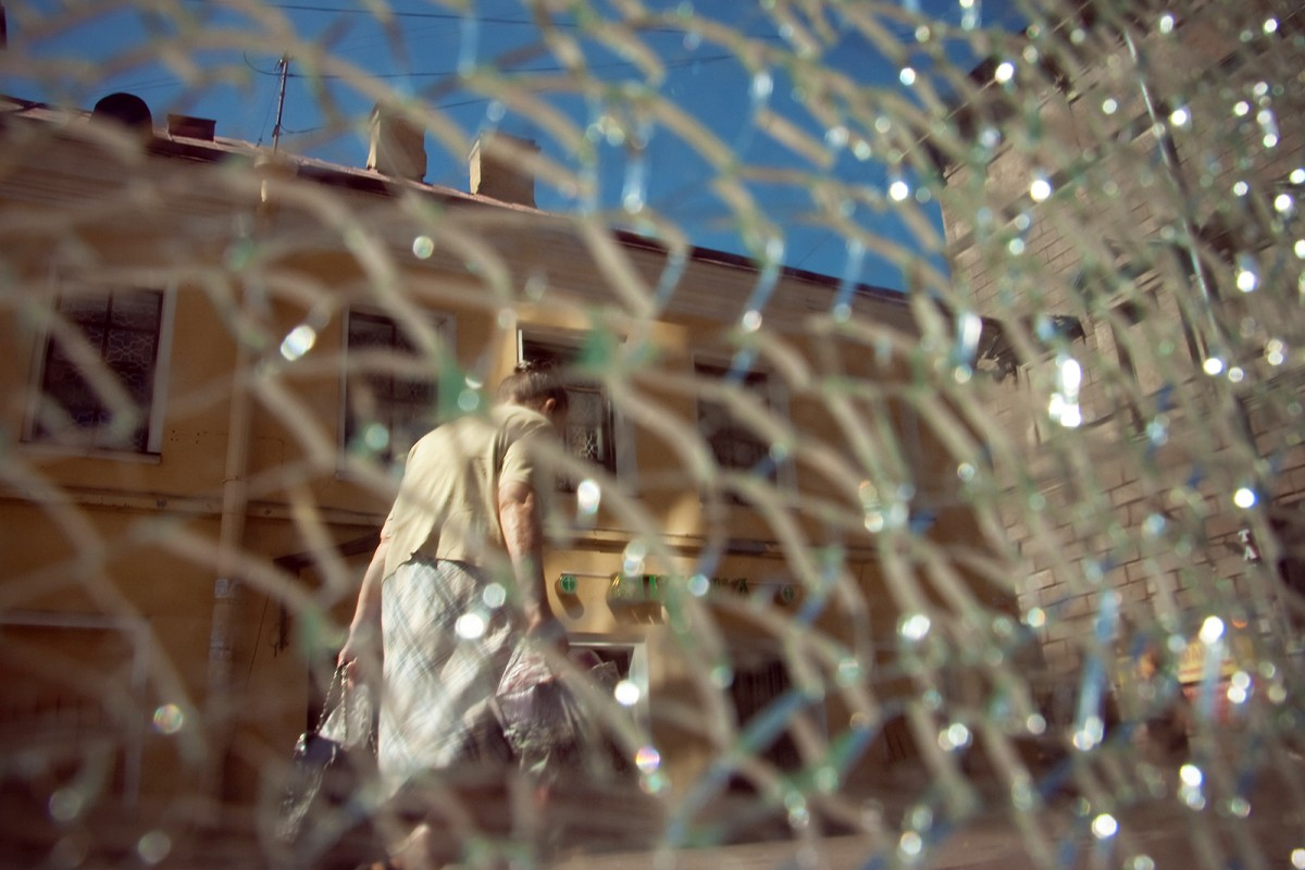 Old woman with shopping bags over broken glass