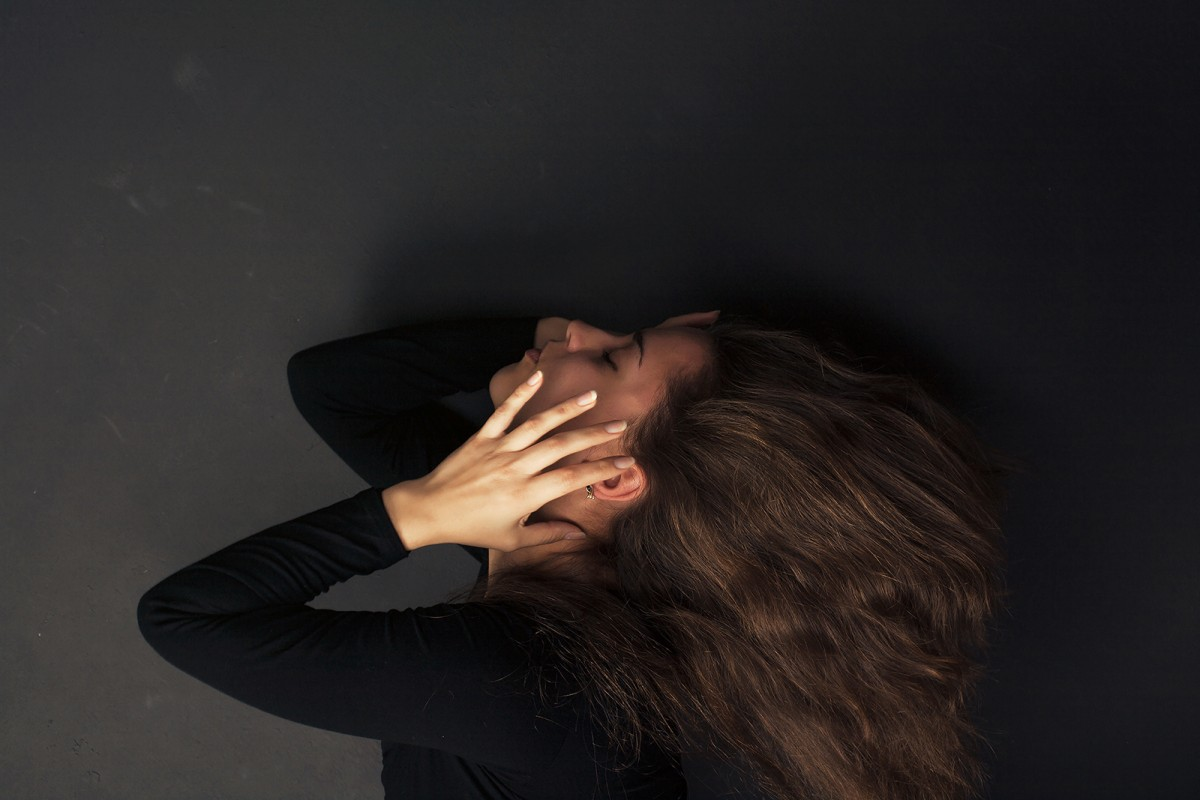Beautiful sad woman on a dark background