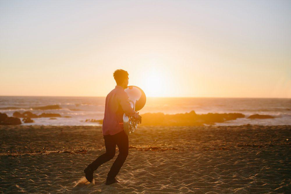 Musician with Tuba instrument run on sea shore on sunset