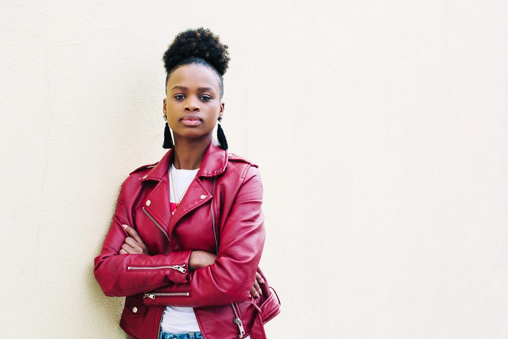 portrait of cheerful black teenage girl with healthy-looking skin and voluminous African hair, dressed in red Leather Jacket on white background